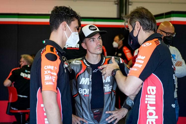 Lorenzo Savadori et Maverick Viñales en conversation avec le directeur de course d'Aprilia Massimo Rivola
